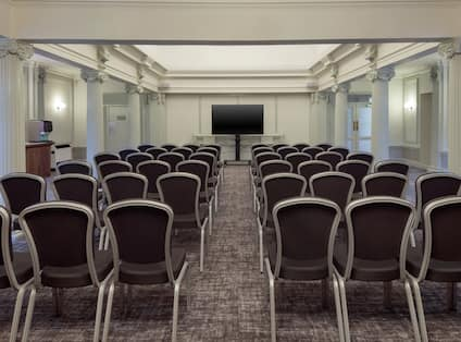 a meeting room with chairs and presentation screen
