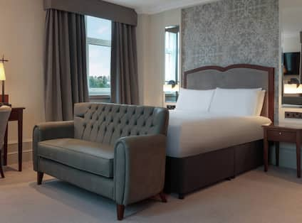 a settee in front of a bed in a hotel room