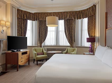 a bed, chairs and a tv in a hotel room