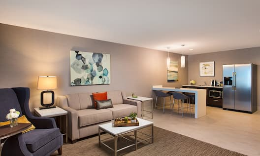 Junior Suite Living Room With Armchair, Side Tables, Wall Art, Sofa Bed, Dining Table With Seating for Two and Kitchen