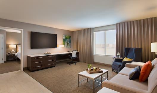 Junior Suite Living Room With Open Doorway to Bedroom, TV, Work Desk in Corner by Window , Armchair, Sofa and Table