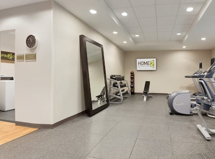 Spin2Cycle With Open Doorway to Laundry Room and Fitness Center With Large Mirror, Free Weights, Weight Balls, TV, Weight Bench, and Cardio Equipment