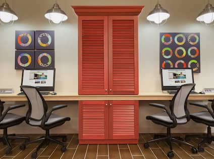 Business Center with Colorful Wall Art, Work Desk, Two Computers, Four Ergonomic Chairs, and Red Storage Cabinet