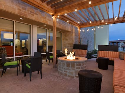 Armchairs With Green Cushions and Striped Sofas by Round Fire Pit on Illuminated Outdoor Patio at Night