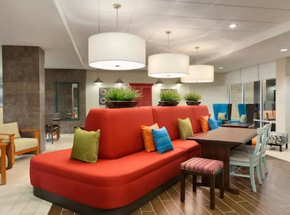 Oasis Lobby Area With Large Red Sofa, Armchairs Decorative Lighting and Table by Windows