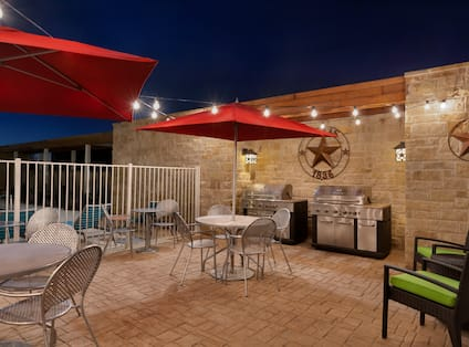 Two Tables With Red Umbrellas and Chairs, Soft Seating, and Two Barbecue Grills on Illuminated Outdoor Patio at Night