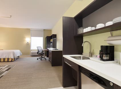 Kitchen, TV, TV, Work Desk by Window, Queen Bed With Illuminated Lamp on Bedside Table in Accessible Studio Suite