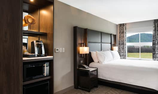 Hospitality Center, King Bed Between Two Illuminated Lamps and Bedside Tables, and Window With Open Drapes in Accessible Room