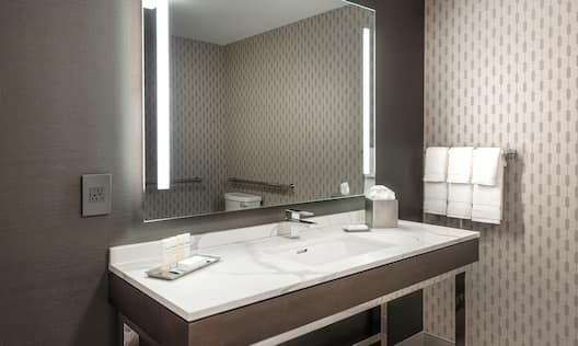 Reflection of Toilet With Grab Bars in Large Vanity Mirror, Sink, Towels, Toiletries, and Amenities