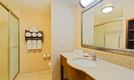 Shower With Glass Door, Fresh Towels, Toilet, Vanity Mirror, Sink, Towels, and Toiletries in Guest Bathroom
