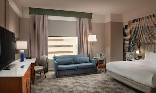 Guest Room with Large Bed Sofa HDTV and Work Desk