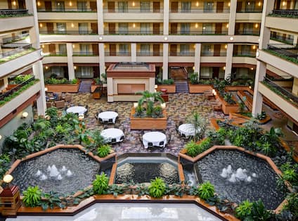 overview of hotel atrium, dining tables, water fountains
