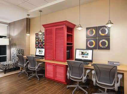 Illuminated Floor Lamp and Black and White Lounge Chair in Corner by Window, Colorful Wall Art, Red Storage Cabinet Between Two Computers on Long Desk, and Four Ergonomic Chairs in Business Center