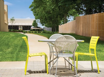 Grassy Outdoor Area by Fence With Table and Four Chairs
