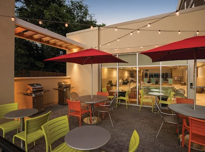 Illuminated Outdoor Patio With Chairs, Red Umbrella Tables, and Two Barbecue Grills at Dusk