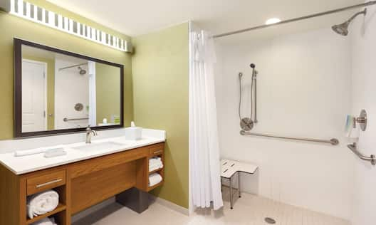 Large Vanity Mirror, Sink, Fresh Towels and Toiletries, Roll-In Shower With Seat, Grab Bars, Handheld Showerhead in Accessible Bathroom