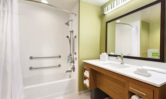 Accessible Bathtub With Handheld Showerhead, Handrails, Large Vanity Mirror, Sink, and Toiletries