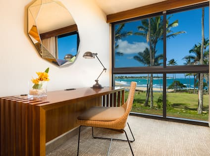 Faceted Mirror Above Work Desk With Lamp, Fresh Flowers, and Chair by Large Window With Ocean View