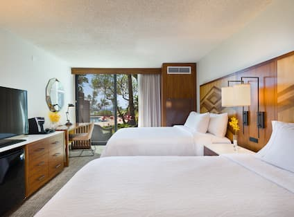 Lanai Room With Two Queen Beds, Headboard Lamps, Bedside Table, Mini Fridge, TV, Keurig, and Faceted Mirror Above Work Desk by Patio Door With Ocean View