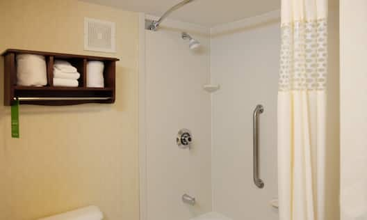 Guestroom bathroom shower with handrail, toilet, and towels