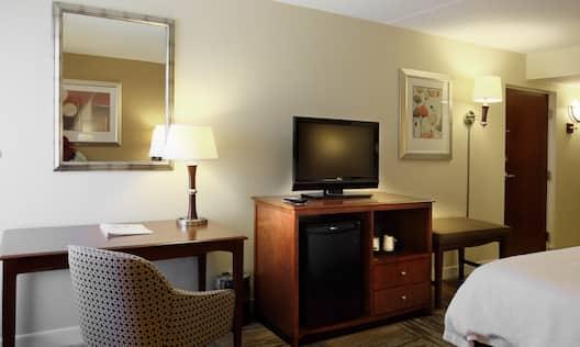 Guestroom with work desk, TV, mini fridge, and room entrance