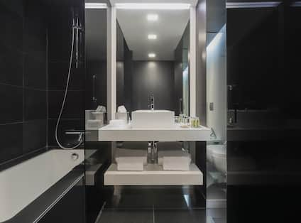 Bathroom with Vanity with Towels and Amenities and Bathtub