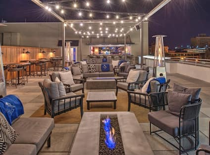 Outdoor Patio Area with Chair, Sofas and Firepit at Night