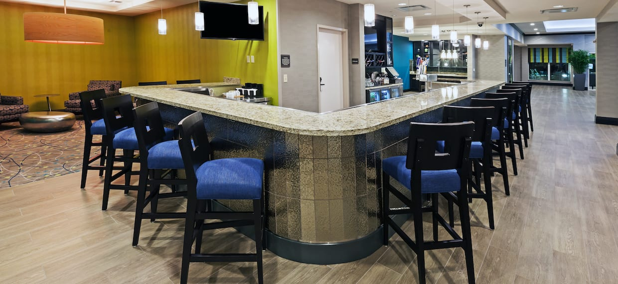 Bar With Blue Chairs at Counter, TV, and Lounge Area With Silver Table and Soft Seating