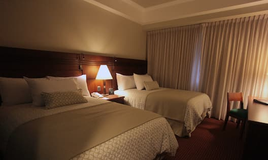 Executive Suite Bedroom With Two Queen Beds, TV, and Work Desk by Window With Closed Drapes