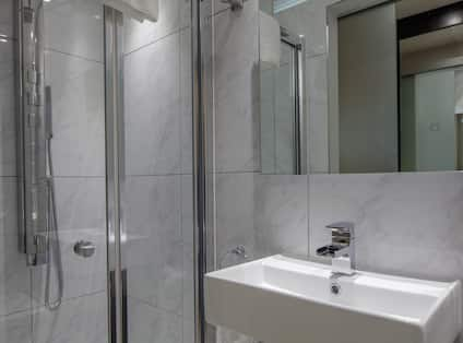 Shower With Glass Doors, Vanity Mirror and Sink in Family Bathroom