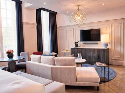 Suite with bed, footrest, lounge sofa, and TV