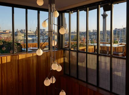 Light chandelier in Rooftop restaurant stairway entrance, with view of city through high windows