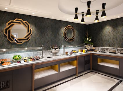 Wall Art Above Counter With Plates, Utensils, Hot and Cold Buffet Items in Breakfast Room