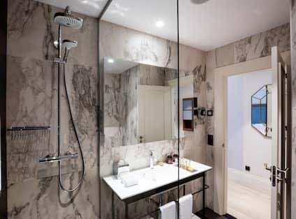 Shower With Glass Doors, Large Vanity Mirror, Sink, Fresh Towels, and Toiletries in Superior Bathroom With Open Doorway to Bedroom