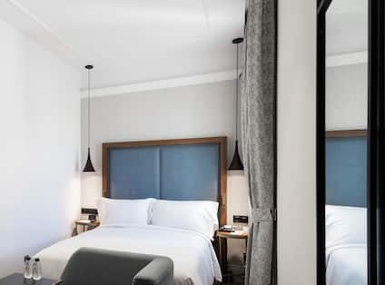 Double Bed, Bed Bench, Illuminated Lamps Above Bedside Tables, Window With Long Drapes, and Large Mirror in Guest Room