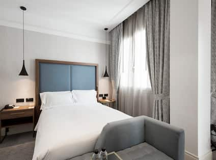 Queen Bed, Bed Bench, Illuminated Lamps Above Bedside Tables, and Window With Long Drapes in Guest Room