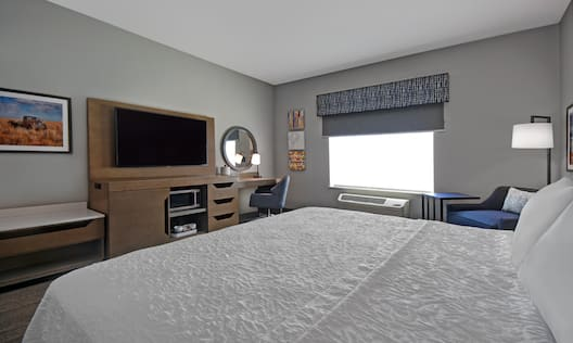 guest room with bed window television and work desk