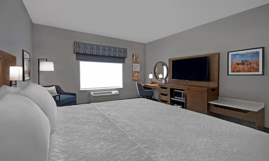 guest room with bed television work desk and window