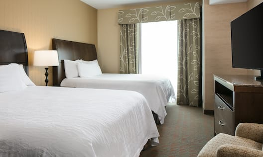 2 beds in room with TV