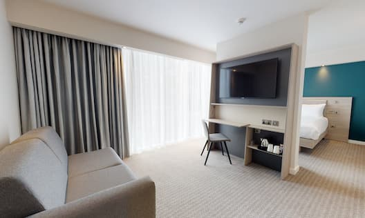 Queen Room With City View Sofa And TV