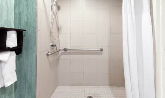 Accessible Guest Room Bathroom with Roll-in Shower and Fresh Towels