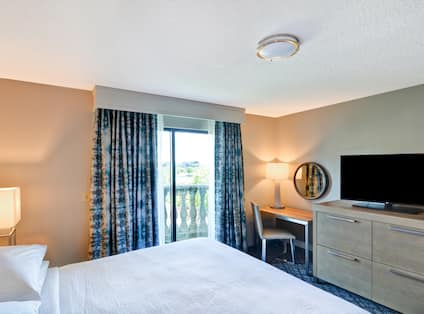 Suite Bedroom with King Bed, Work Desk, Television, Outside View and Balcony
