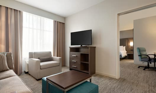 Suite living area with sofa, soft chair, coffee table, ottoman, TV, and partial view into bedroom