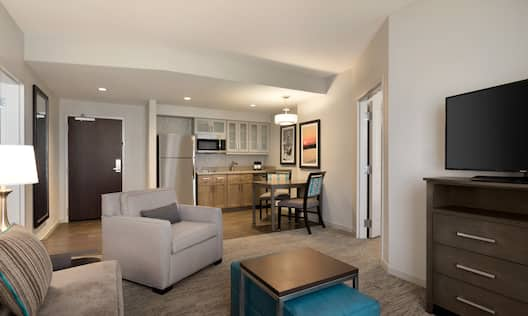 Suite living area with sofa, soft chair, coffee table, ottoman, TV, and partial view of kitchen and room entrance