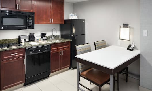 Guestroom Kitchen with Appliances and Dining Table