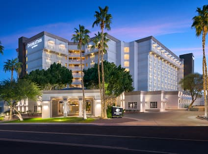 Hotel Exterior in the Evening with DoubleTree Sign and Palm Trees