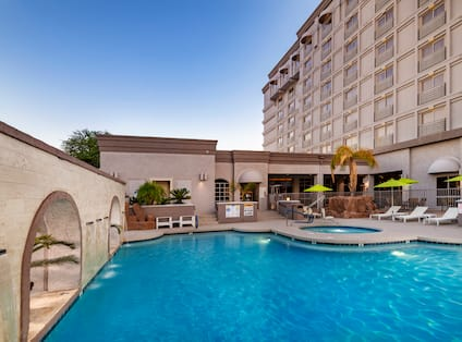 Outdoor Pool and Whirlpool Area with Recliners and Umbrellas