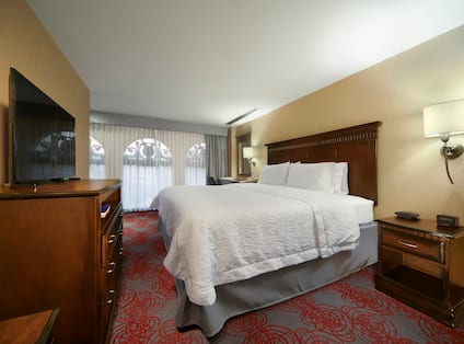 Standard King bed with large widows in the back ground a TV to the left and a small table next to the bed, on the right wall.