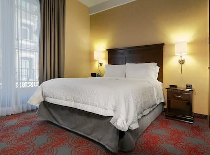 Standard queen bed on right wall with large window to the left and small side table to the right.