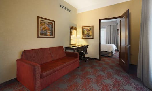 King suite living area with red couch on the left wall.
